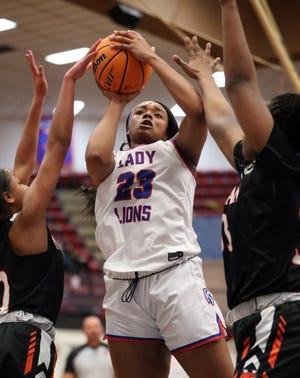 MooreÕs Aaliyah Moore shoots between two defenders during a high school girls basketball game between the Moore Lions and the Norman Tigers at Moore High School on Jan. 14, 2021 in Moore, Okla. [Steve Sisney/For The Oklahoman]