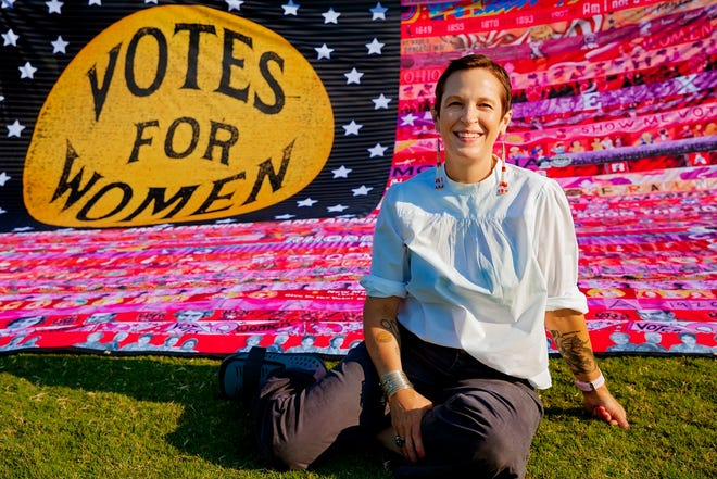 """Oklahoma artist Marilyn Artus poses for a photo with her completed multi-year """"Her Flag"""" project commemorating the 100th anniversary of th 19th Amendment at Scissortail Park in Oklahoma City, Okla. on Friday, Aug. 21, 2020. [Chris Landsberger/The Oklahoman Archives]"""