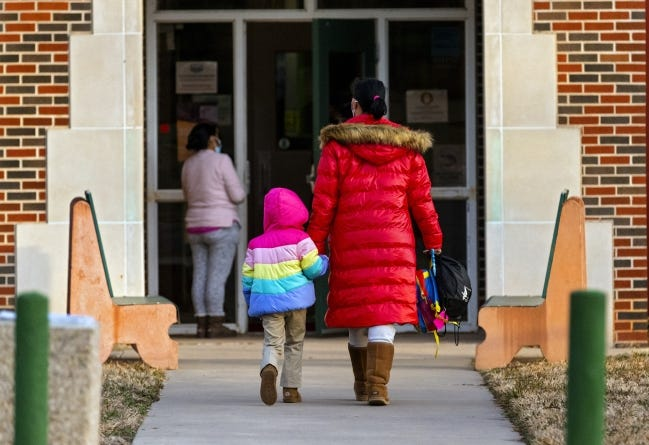 A parent and child walk to Gatewood Elementary in Oklahoma City on Jan. 19. Oklahoma City Public Schools is considering having students attend classes in person four days a week instead of two. [Chris Landsberger/The Oklahoman]