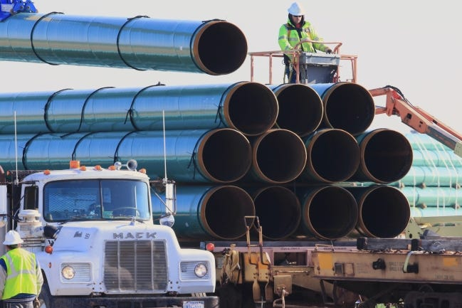 Workers unload pipe in South Dakota in 2015 as construction continued on the Dakota Access pipeline. On Thursday, the acting Secretary of Interior issued a suspension of any ongoing work the agency was doing to permit future energy recovery activities from federal reserves, both on- and off-shore. [AP Photo/Nati Harnik]