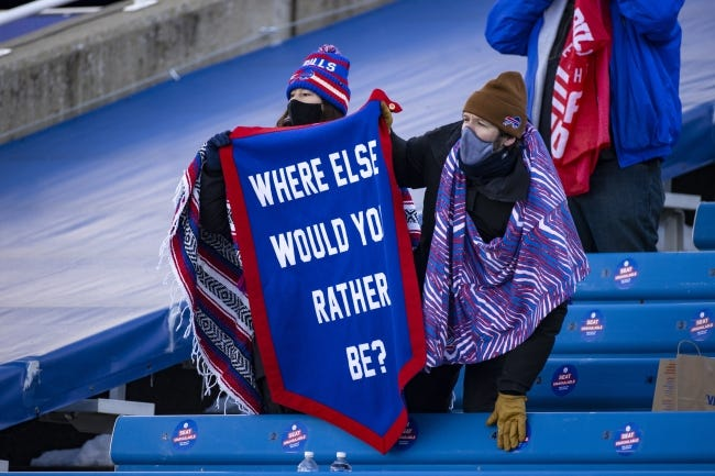 """Bills fans hold a pennant reading """"where else would you rather be?"""" before an NFL wild-card playoff game against the Colts on Jan. 9 in Orchard Park, N.Y. [AP Photo/Brett Carlsen]"""