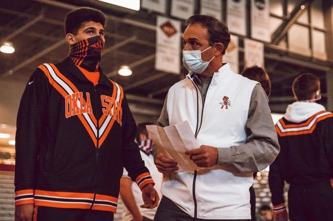 Oklahoma State wrestling coach John Smith, talks, with freshman A.J. Ferrari earlier this season. [OSU ATHLETICS]