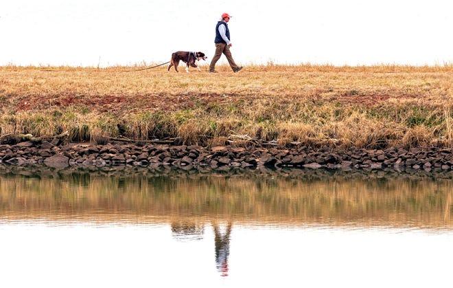 A person walks with their dog beside Lake Overholser in Oklahoma City on Thursday. [Chris Landsberger/The Oklahoman]