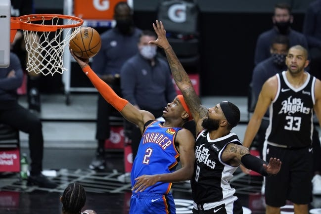 Thunder guard Shai Gilgeous-Alexander (2) goes for a layup past Clippers forward Marcus Morris Sr. (8) during the fourth quarter of a 120-106 loss Friday night in Los Angeles. [AP Photo/Ashley Landis]