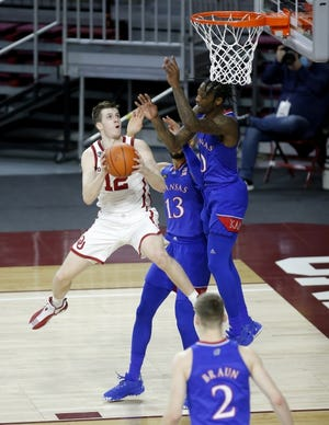 Oklahoma's Austin Reaves, left, goes to the basket against Kansas earlier this season. Reaves missed the past two games due to COVID-19 protocols but is expected to return Saturday. [Sarah Phipps/The Oklahoman]