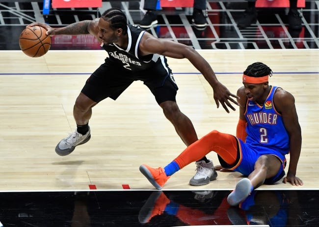 Clippers forward Kawhi Leonard (2) picks up a loose ball as Thunder guard Shai Gilgeous-Alexander (2) falls to the floor during the first quarter of Los Angeles' 108-100 win Sunday at Staples Center. [Robert Hanashiro/USA TODAY Sports]