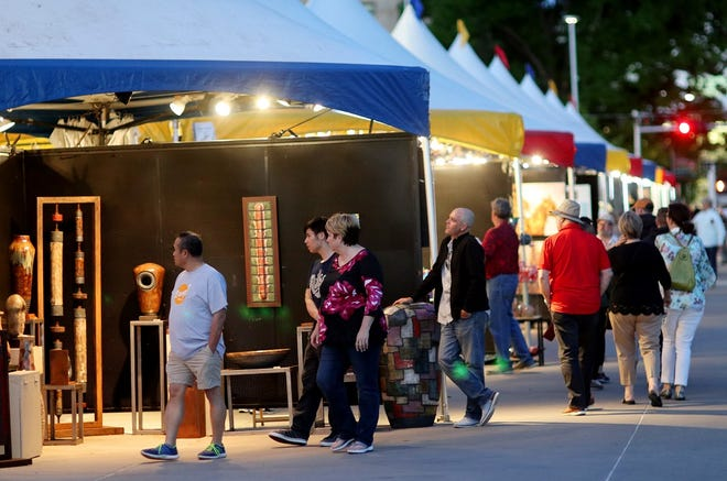 People look at artwork displayed in a row of tents along Colcord Drive at the 2019 Festival of the Arts in Bicentennial Park in downtown Oklahoma City, Thursday, April 25, 2019. [Doug Hoke/The Oklahoman Archives]