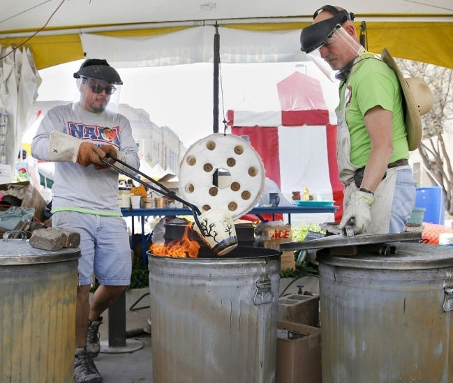 Hector Cobos Leon places a piece of pottery in a reduction chamber next to Collin Rosebrook, owner of Paseo Pottery, at Pottery Place during the 2018 Festival of the Arts in downtown Oklahoma City, Thursday, April 26, 2018. [The Oklahoman Archives]
