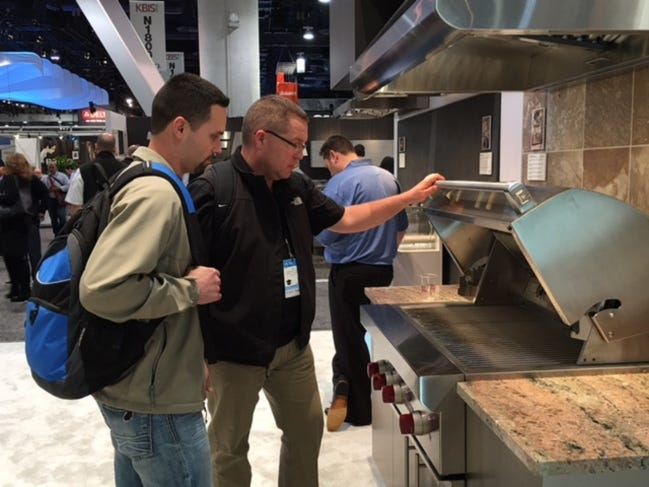 Dan Reeves, right, owner of Landmark Fine Homes, and employee Jason Underhill look at new products on display at the 2016 International Builders' Show in Las Vegas. [PHOTO PROVIDED]