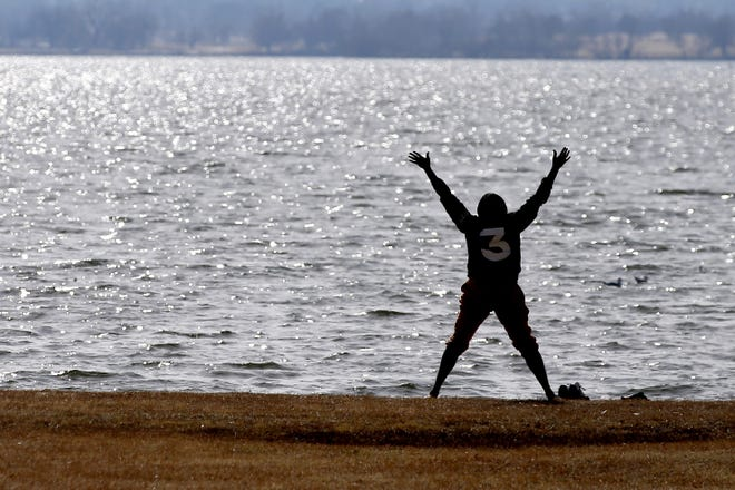 Lloyd Stephenson does yoga along the shore of Lake Hefner in Oklahoma City on Thursday. Stephenson, a marathon runner, said he enjoys meditating under the sun and being outside is his thing. [Bryan Terry/The Oklahoman]