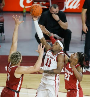 Oklahoma's De'Vion Harmon (11) passes the ball from between Alabama's Alex Reese (3) and John Petty Jr. (23) during a college basketball game between the University Oklahoma Sooners (OU) and the Alabama Crimson Tide at Lloyd Noble Center in Norman, Okla., Saturday, Jan. 30, 2021. Oklahoma won 66-61. [Bryan Terry/The Oklahoman]