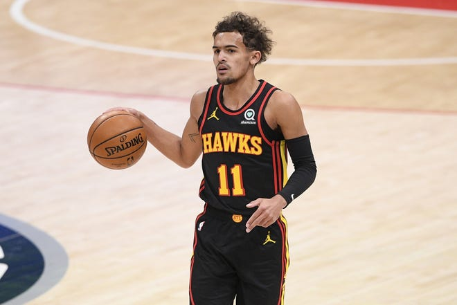 Hawks guard Trae Young (11) dribbles the ball during the first half against the Wizards on Friday in Washington. [AP Photo/Nick Wass]