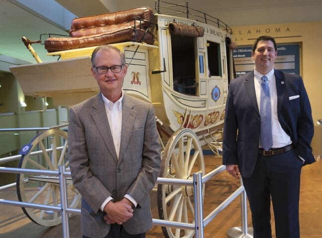 Bob Blackburn and his successor, Trait Thompson, stand in front of a stagecoach at the Oklahoma History Center. [Doug Hoke/The Oklahoman]