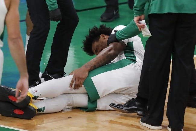 Boston's Marcus Smart grabs his leg during the second half of Saturday's game against the Los Angeles Lakers. ESPN reported the former Oklahoma State star suffered a calf sprain that might sideline him for 1-2 weeks. [AP Photo/Michael Dwyer]