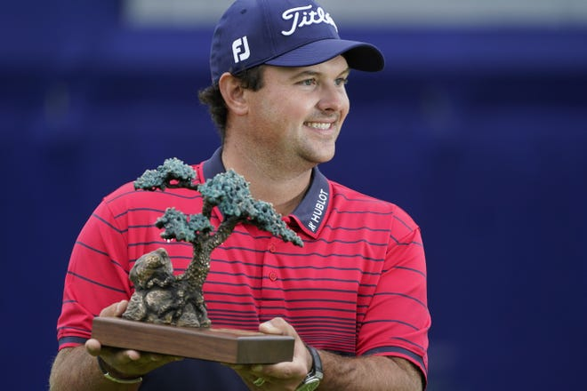 Patrick Reed stands on the South Course while holding his trophy for winning the Farmers Insurance Open golf tournament at Torrey Pines on Sunday in San Diego. [AP PhotoS/Photos by Gregory Bull]