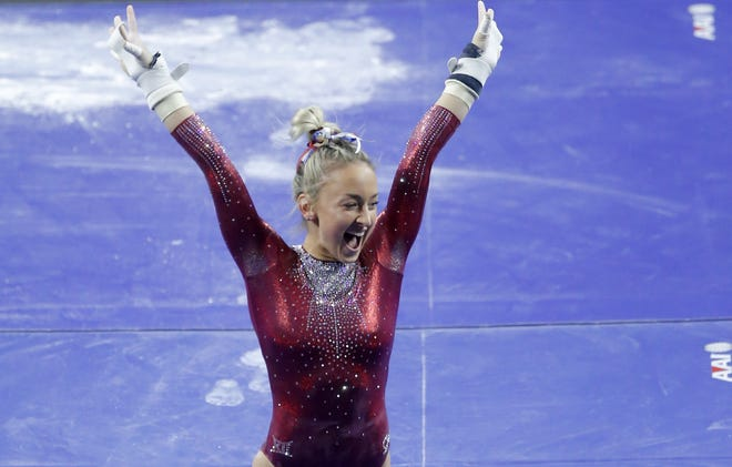 Oklahoma's Audrey Davis celebrates after competing on the uneven bars during a women's gymnastics meet against West Virginia on Sunday night at Lloyd Noble Center in Norman. The Sooners won 195.850-194.775. [Bryan Terry/The Oklahoman]