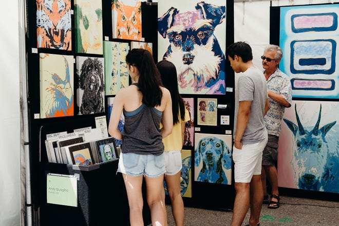 Attendees look at artwork at the Paseo Arts Festival. [Paige Powell photo]