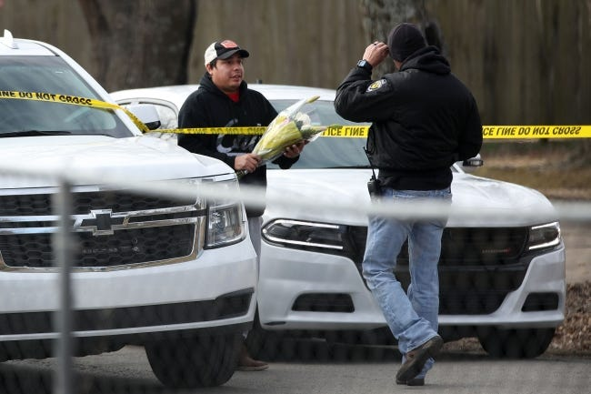 A man gives flowers for a memorial to an investigator at the scene of a suspected mass homicide where at least 5 children were slain Tuesday, Feb. 2, 2021 in Muskogee, Okla. [Photo by Mike Simons, Tulsa World]