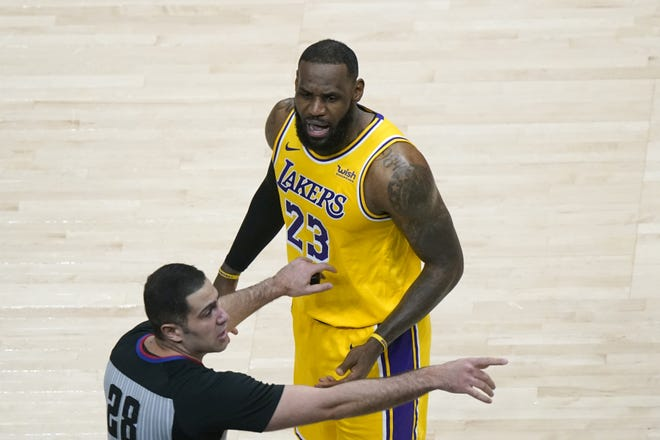 Los Angeles Lakers forward LeBron James (23) is restrained by an official as he reacts to a fan in the second half Monday at Atlanta. [AP Photo/John Bazemore]