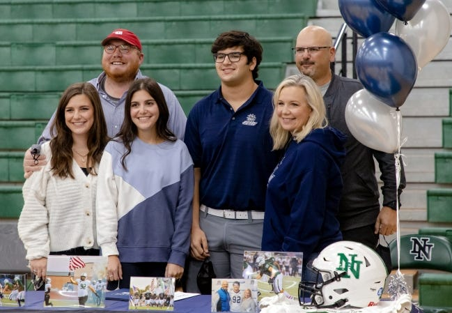 Pierce Hassen, center, smiles with his family after Signing Day ceremonies at Norman North High school. The defensive lineman missed all of his junior season after a car accident caused serious injury to his left hand, but extensive physical therapy, thickly padded gloves and high pain tolerance got him back on the field this past season. [CHRIS LANDSBERGER/THE OKLAHOMAN]