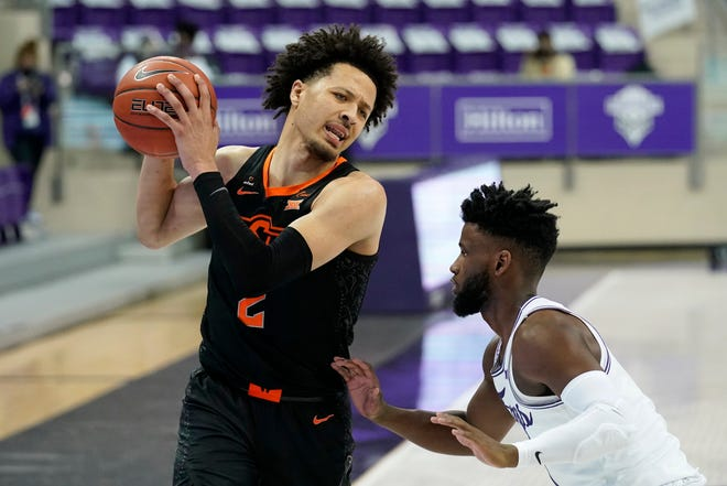 Oklahoma State guard Cade Cunningham (2) looks for an opening to the basket as TCU's Mike Miles defends during the first half of an NCAA college basketball game in Fort Worth, Texas, Wednesday, Feb. 3, 2021. (AP Photo/Tony Gutierrez)