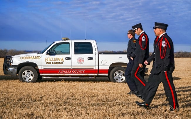 Members of the Elk City Fire Department, wearing ceremonial dress, walk in front of a Helena Fire Department truck on Friday. Firefighters from across the state attended the funerals of two Waynoka firefighters who died Jan. 29. [Jordan Green/For The Okahoman]