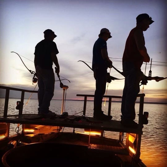 Bowfishermen search for fish from a custom-designed boat equipped with flood lights, trolling motor, and raised platform for night bowfishing. [PHOTO PROVIDED BY CALEB TURCOTTE]