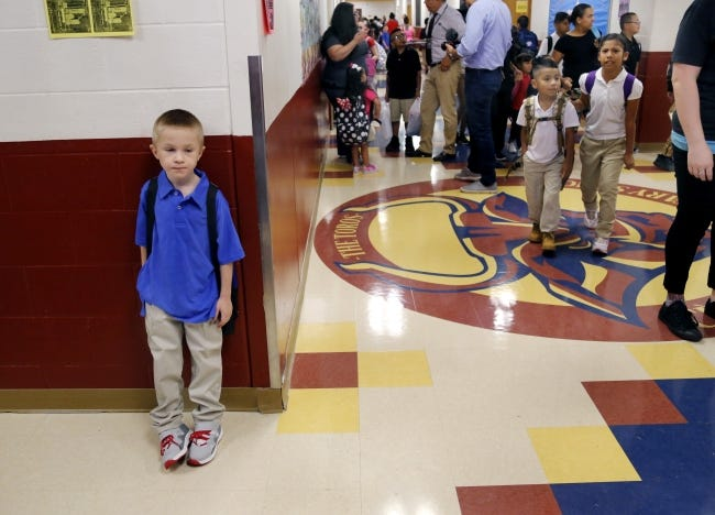 """A boy stands against the wall in the main hallway of Cesar Chavez Elementary in Oklahoma City on the first day of school in 2018. Gov. Kevin Stitt and Republican lawmakers say they support changing the way school funding is distributed to avoid dedicating money to """"ghost students."""" [The Oklahoman Archives]"""