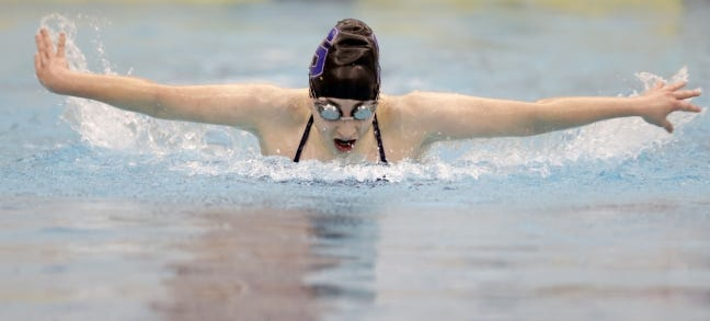 Stillwater's Emily Carman competes in the girls 100-yard butterfly during the Class 6A East Girls Regional at the Jenks Trojan Aquatic Center on Saturday. [John Clanton/Tulsa World]