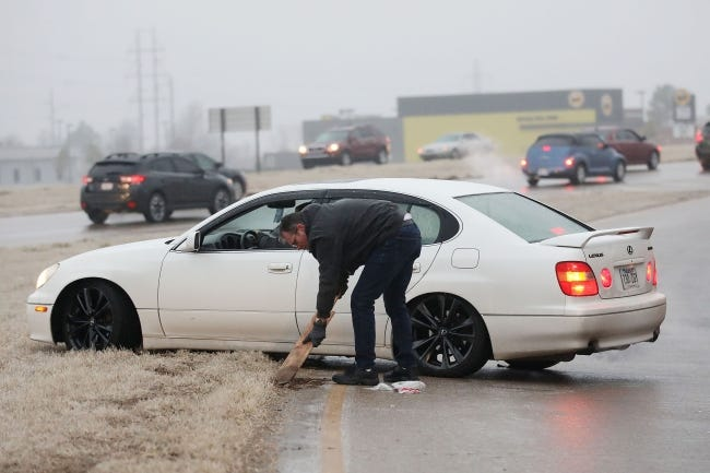 A man works to free a stuck motorist on the 96th Street North on ramp to U.S. 169 on Monday in Owasso. The ramp and highway were backed up due to freezing rain and ice. [MIKE SIMONS/TULSA WORLD]
