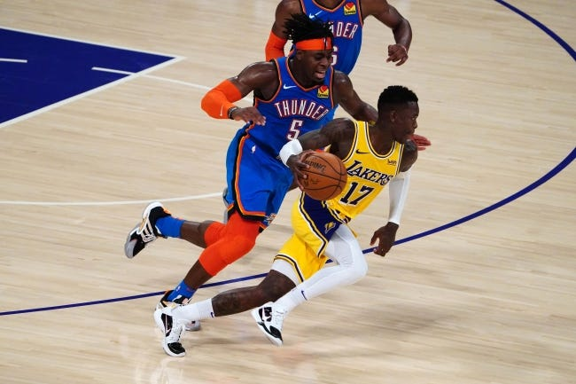 Feb 8, 2021; Los Angeles, California, USA; Los Angeles Lakers guard Dennis Schroder (17) is pursued by Oklahoma City Thunder forward Luguentz Dort (5) in overtime at Staples Center. The Lakers defeated the Thunder 119-112 in overtime. Mandatory Credit: Kirby Lee-A TODAY Sports