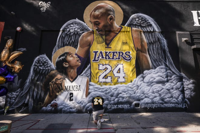 Adam Dergazarian, bottom center, pays his respects for the late Kobe Bryant and his daughter, Gianna, in front of a mural painted by artist Louie Sloe Palsino on Jan. 26 in Los Angeles. [AP Photo/Jae C. Hong, File]