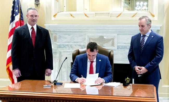 House Speaker Charles McCall, left, and President Pro Tem Greg Treat look on as Gov. Kevin Stitt signs Senate Bill 1031, his first bill of the legislative session, at the Oklahoma state Capitol in Oklahoma City, Okla. on Wednesday, Feb. 10, 2021. The bill will temporarily allow public bodies to meet virtually during the COVID-19 pandemic. [Chris Landsberger/The Oklahoman]