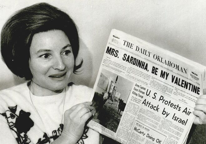 """Ginette Sardinha, of Midwest City, receives a valentine's surprise from her husband via the front page of The Daily Oklahoman in 1970. Carlos Sardinha, who was stationed in Korea with the U.S. Air Force, had written to the newspaper, asking The Daily Oklahoman if it could deliver a paper to his wife with a special valentine's headline. On the eve of Valentine's Day, his request was granted. Toward the end of the regular press run for the Feb. 13, 1970, edition, the front page was changed with the addition of the headline """"Mrs. Sardinha, Be My Valentine."""" Under the headline was excerpted text from the two-page letter her husband had written to the newspaper. The couple had met in Paris in 1954 while he was stationed in France. [JOE AKER/THE OKLAHOMAN ARCHIVES]"""