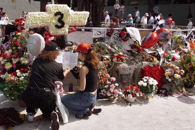 Two Dale Earnhardt fans kneel and read one of the many letters and kind words placed at the Dale Earnhardt memorial in Daytona Beach, Fla., on Feb. 20, 2001, as hundreds of fans crowd the area to pay their last respects to the beloved driver. [Kelly Jordan/Daytona Beach News-Journal]