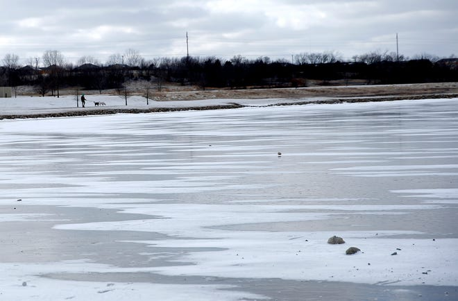A person walks dogs around the frozen pond in front of the Meridian Technology Center in Stillwater, Okla., Saturday, Feb. 13, 2021. Photo by Sarah Phipps, The Oklahoman