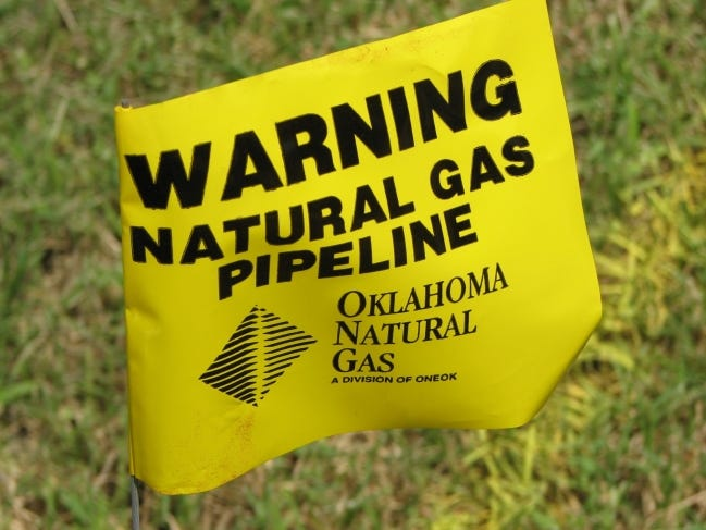 A flag marks the location of a natural gas pipeline during a time when the weather was warmer. During the current winter weather, natural gas companies are asking customers to conserve gas to avoid chances of shortages. [The Oklahoman Archives]