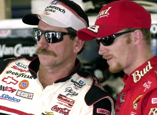 NASCAR drivers Dale Earnhardt, left, and his son Dale Jr., stand together during a break in practice at the Daytona International Speedway on Feb. 9, 2001. [AP Photo/Paul Kizzle, File]