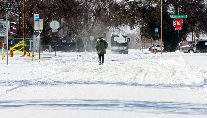 A person walks down a snow packed road in Oklahoma City, Okla. on Monday, Feb. 15, 2021. [Chris Landsberger/The Oklahoman]