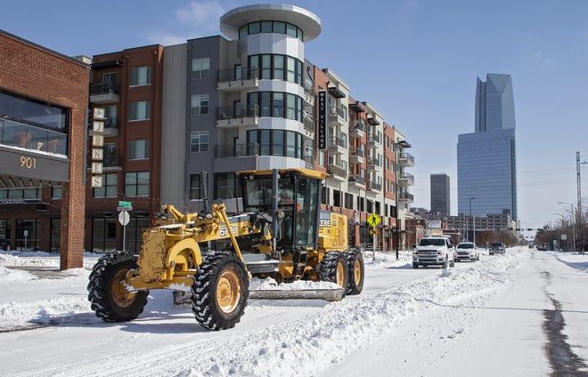 Crews work to remove snow Monday from Sheridan Avenue in Oklahoma City. [Chris Landsberger/The Oklahoman]