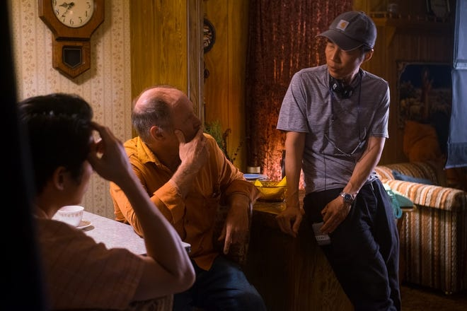 """Director and writer Lee Isaac Chung, right, talks with actors  Steven Yeun, left, and Will Patton on the set of """"Minari,"""" which filmed in Tulsa in 2019. [Joe Rushmore/A24]"""