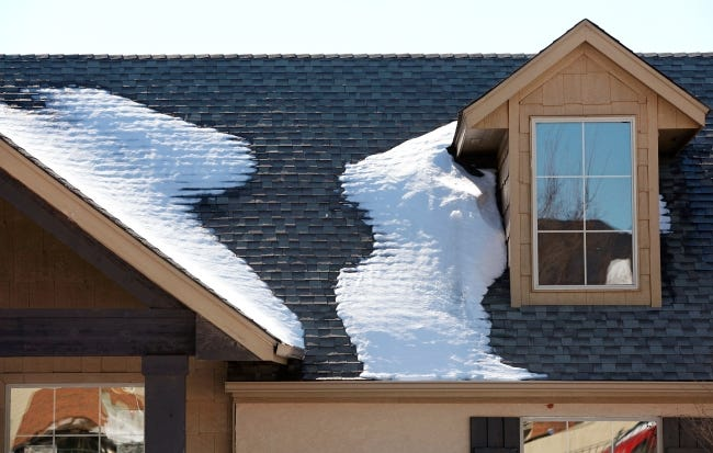 Snow accumulated on an Edmond home's roof during a previous winter storm. Ice damming can result, causing roof damage and leaks. [THE OKLAHOMAN ARCHIVES]