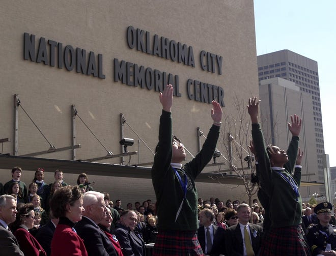 Nichols Hills Elementary School choir students raise their hands to the sky as they perform during the dedication of the Oklahoma City National Memorial Center on Feb. 19, 2001. The center was designed as part of the memorial about the April 19, 1995, bombing of the Alfred P. Murrah Federal Building. Among those attending the dedication 20 years ago were President George W. Bush and first lady Laura Bush, as well as many state and community leaders, bombing survivors and family members of those who had died. In 2003, the lettering on the outside of the building was changed to the Oklahoma City National Memorial Museum. [BRYAN TERRY/THE OKLAHOMAN ARCHIVES]
