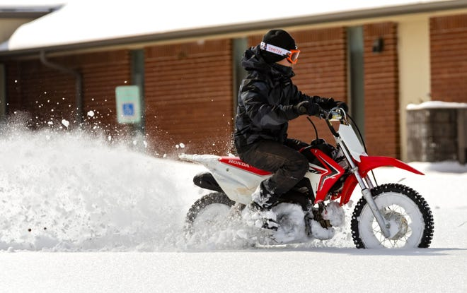 A person rides a motorcycle through the snow in Oklahoma City on Wednesday. [Chris Landsberger/The Oklahoman]