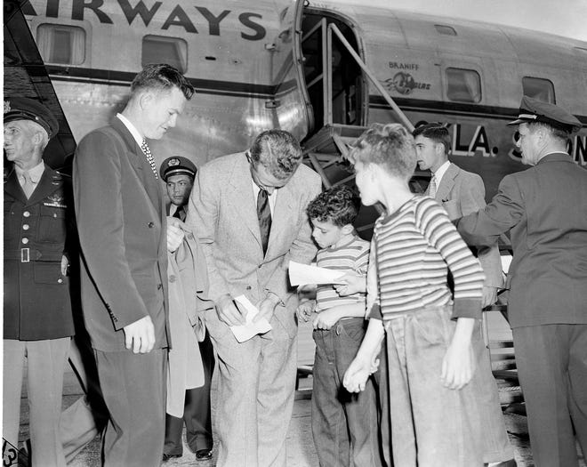 University of Oklahoma coach Bud Wilkinson bends over to sign an autograph for a young fan as the team arrives in Biloxi, Miss., Dec. 27, 1949, for training in preparation for the Sugar Bowl against LSU on January 2. Darrell Royal, quarterback, waits to add his name to the boy's paper. (AP Photo)