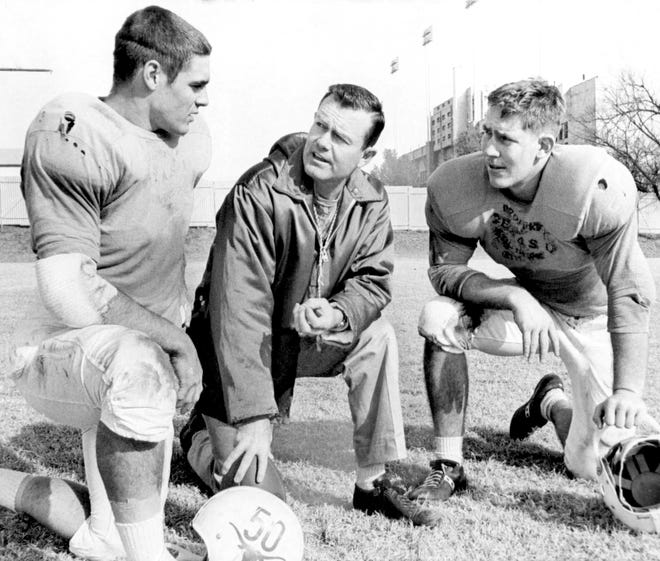 Coach Darrell Royal, center, of the University of Texas, chats with two of the team's captains, David McWilliams, left, and Scott Appleton, tackle, Dec. 27, 1963, in Austin, Texas. (AP Photo/Ted Powers)