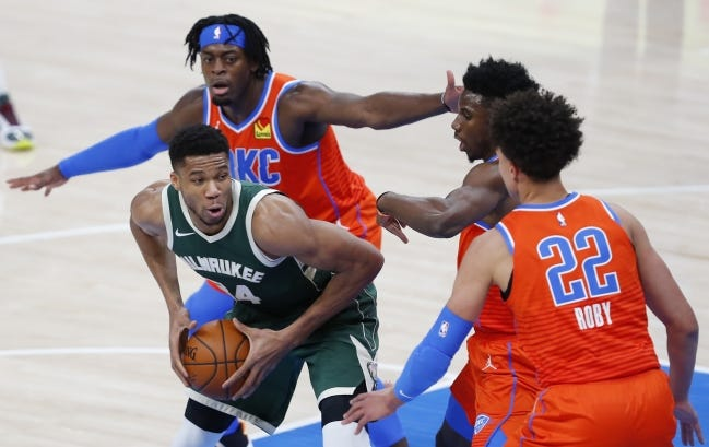 Feb 14, 2021; Oklahoma City, Oklahoma, USA; Milwaukee Bucks forward Giannis Antetokounmpo (34) is defended by Oklahoma City Thunder forward Luguentz Dort (5), guard Hamidou Diallo (6) and center Isaiah Roby (22) on a drive to the basket during the first half at Chesapeake Energy Arena. Mandatory Credit: Alonzo Adams-USA TODAY Sports