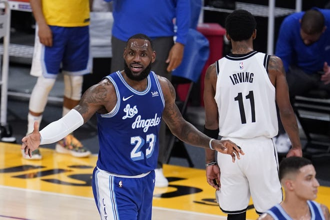 Los Angeles Lakers forward LeBron James argues a call during the first half against the Brooklyn Nets on Thursday. [AP Photo/Marcio Jose Sanchez]