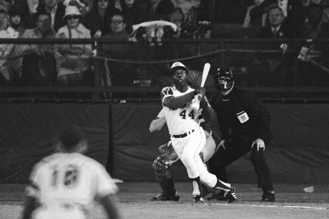 Atlanta Braves outfielder Hank Aaron eyes the flight of the ball after hitting his 715th career homer in a game against the Los Angeles Dodgers on April 8, 1974. Aaron broke Babe Ruth's record of 714 career home runs. [AP Photo/Harry Harris]