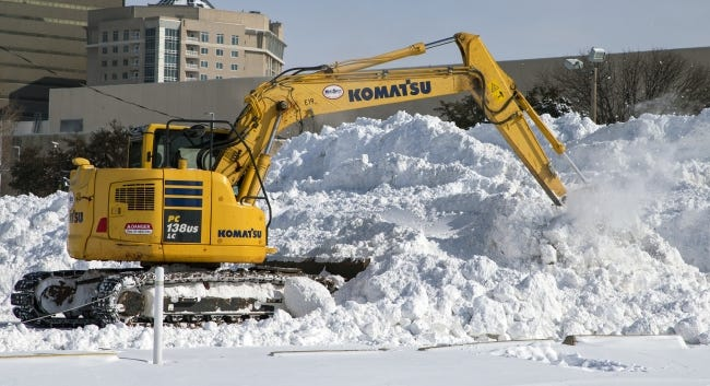 Crews on Feb. 15 work to pile up snow removed from city streets in the parking lot west of the Chesapeake Energy Arena in downtown Oklahoma City. [Chris Landsberger/The Oklahoman]